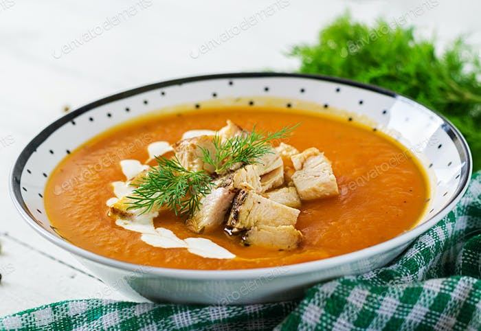 Pumpkin cream soup with pieces of chicken meat. Healthy food. Dinner.