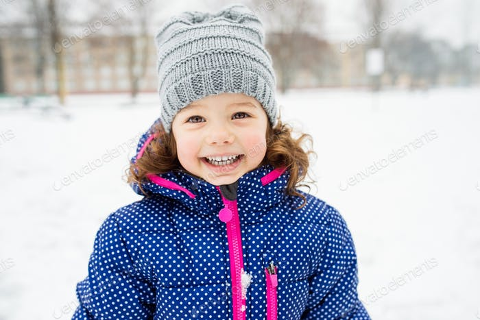Cute little girl playing outside in winter nature