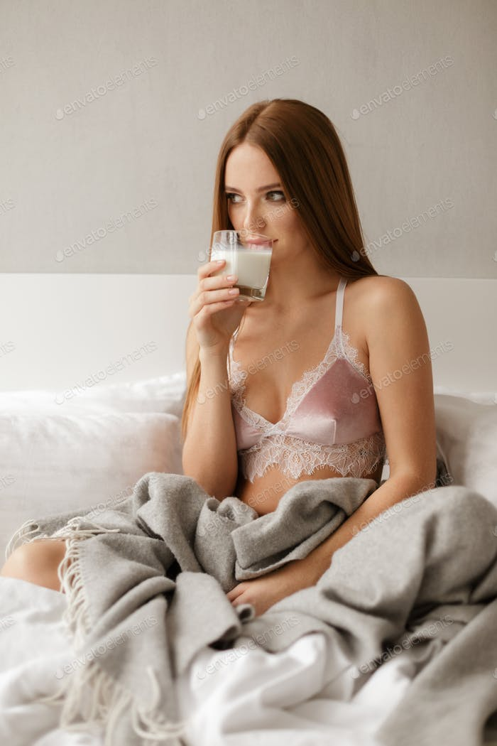 Portrait of beautiful lady sitting in bed with glass of milk in hand and dreamily looking aside