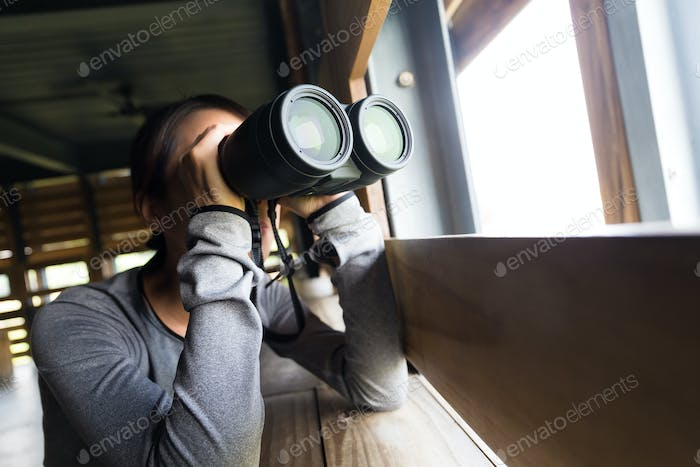 Woman use of the binoculars for birdwatching