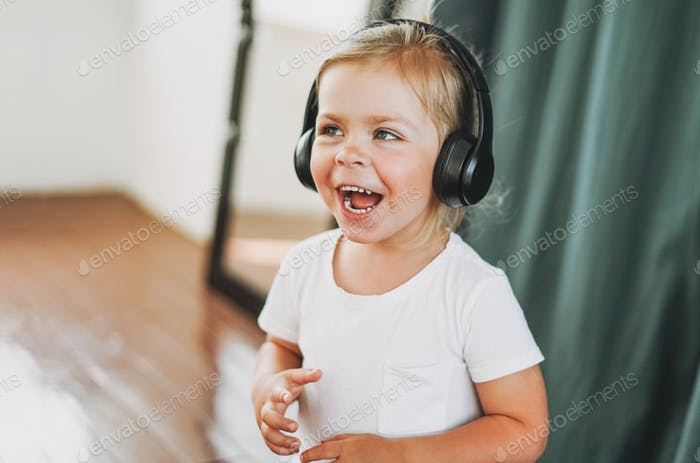 Cute happy toddler girl with fair hair in headphones having fun in bright interior