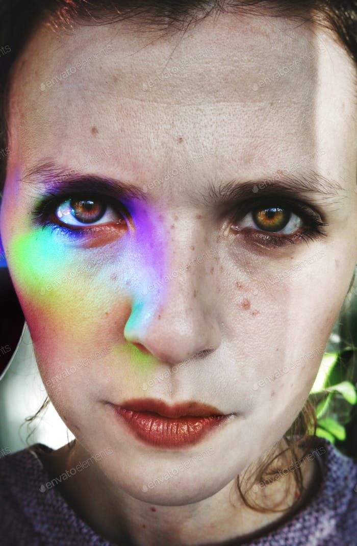 Young woman with a rainbow, shining in her face