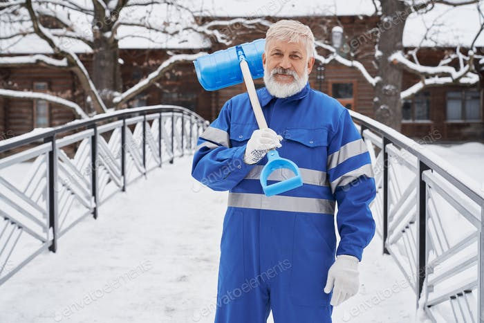 Man with shovel on shoulder looking at camera in winter