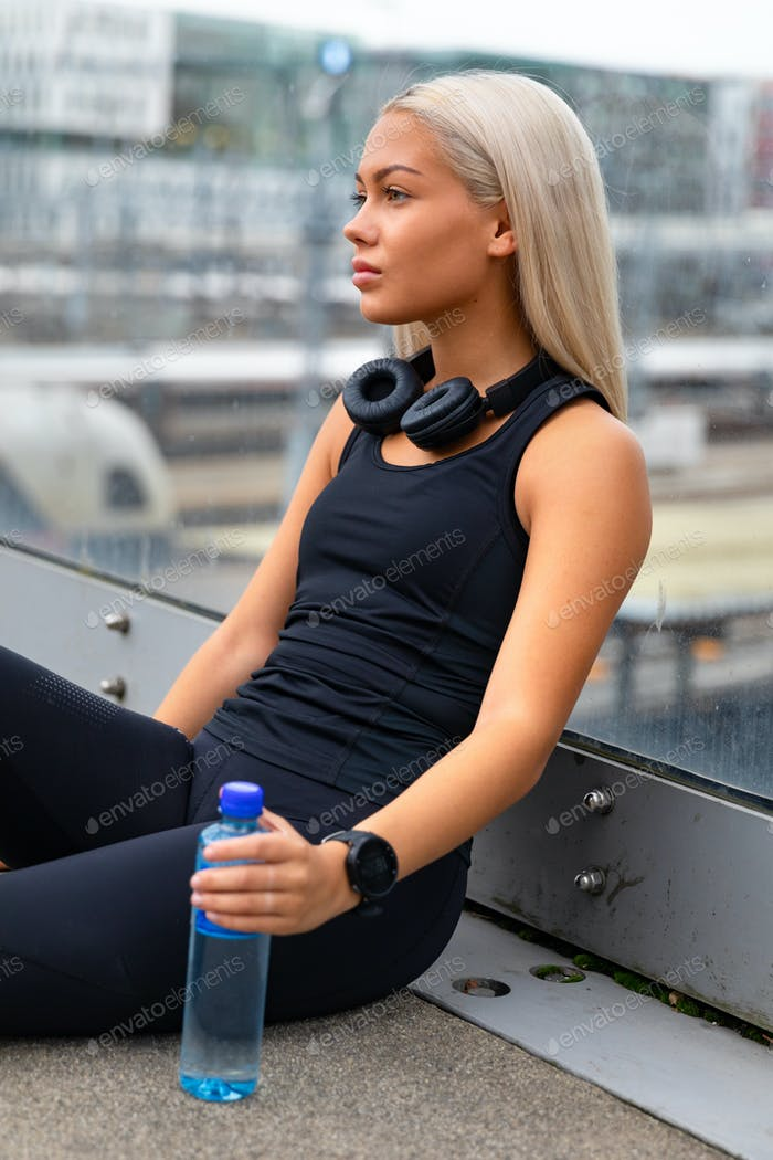 Thoughtful Runner Sitting On Bridge After Workout