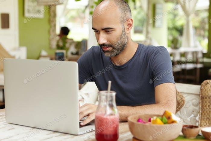 Bärtiger Selbstständiger im mittleren Alter sitzt im Café vor einem generischen Laptop und blickt auf Scre