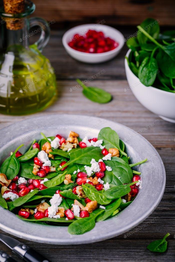 Frischer grüner Salat mit Spinat, Walnüssen, Feta-Käse und Granatapfel
