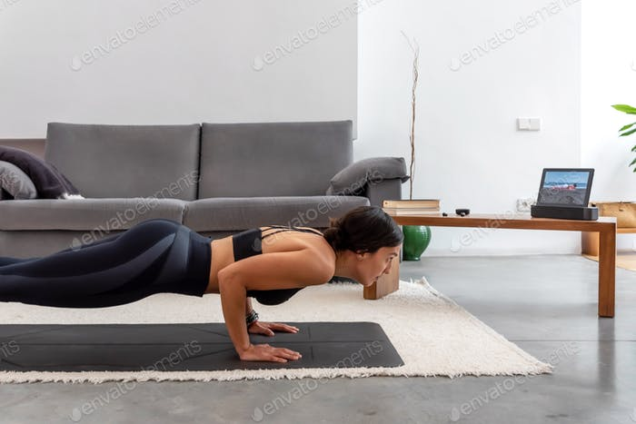 Fit woman practicing Chaturanga pose using online yoga training program in the tablet at home
