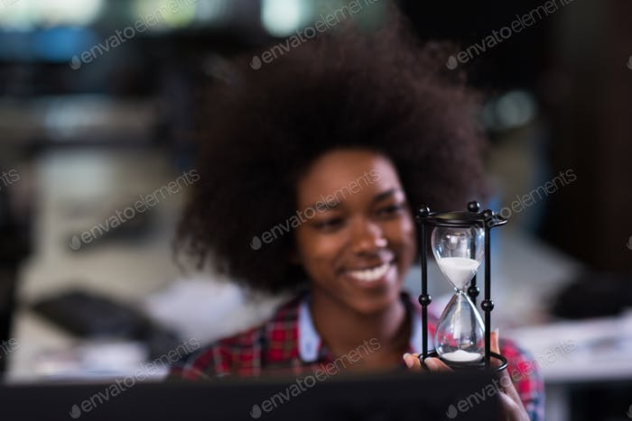 young woman at office looking at sand  clock