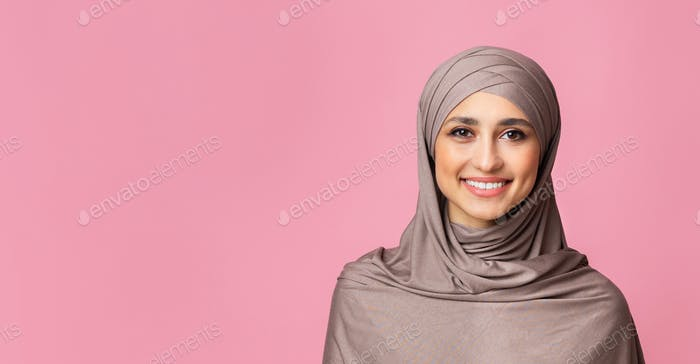 Portrait of smiling islamic woman in hijab over pink background