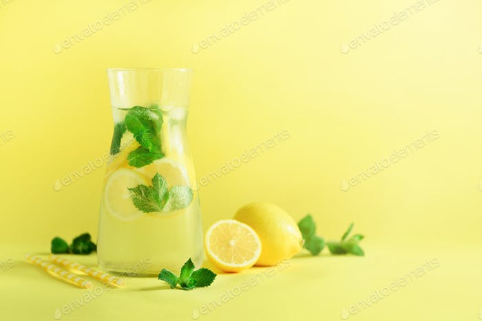 Detox water with mint, lemon on yellow background. Banner with copy space, sunlight bokeh. Citrus