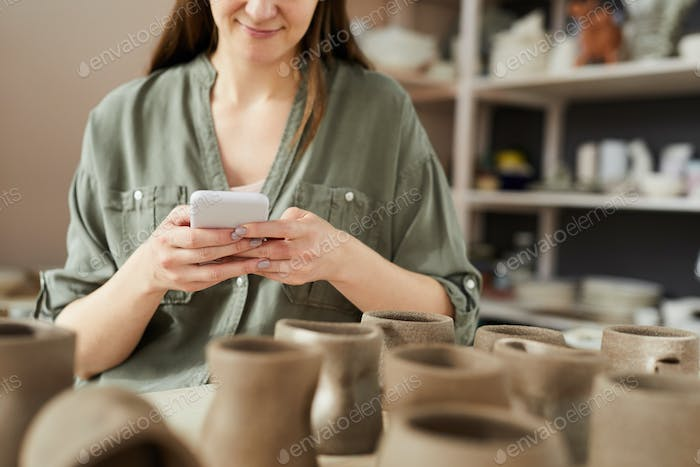 Female Potter Using Smartphone
