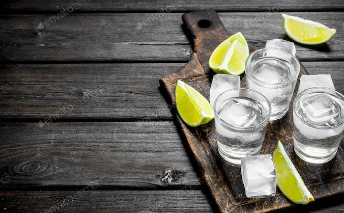 Wodka mit Eis auf einem Schneidebrett mit Limettenscheiben.