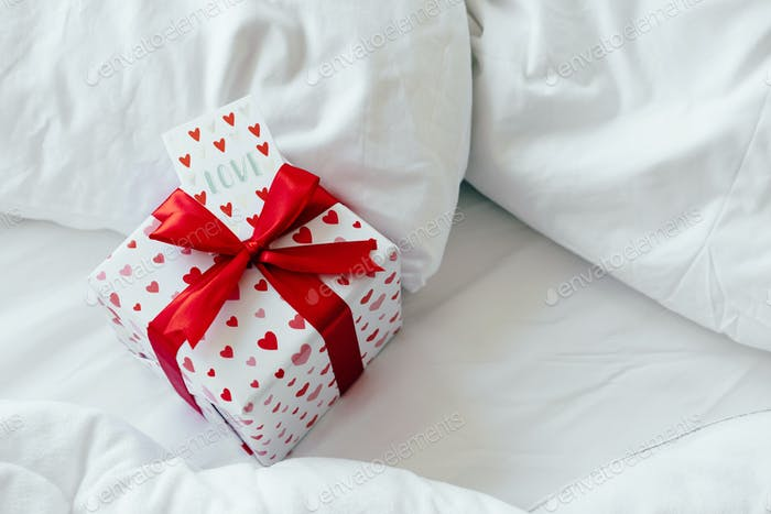 A box with a gift and a valentine card for a loved one lies on the bed