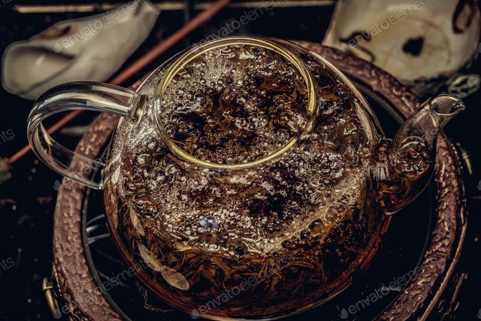 Tea ceremony concept. Close-up image of a process of brewing tea using the glass teapot.