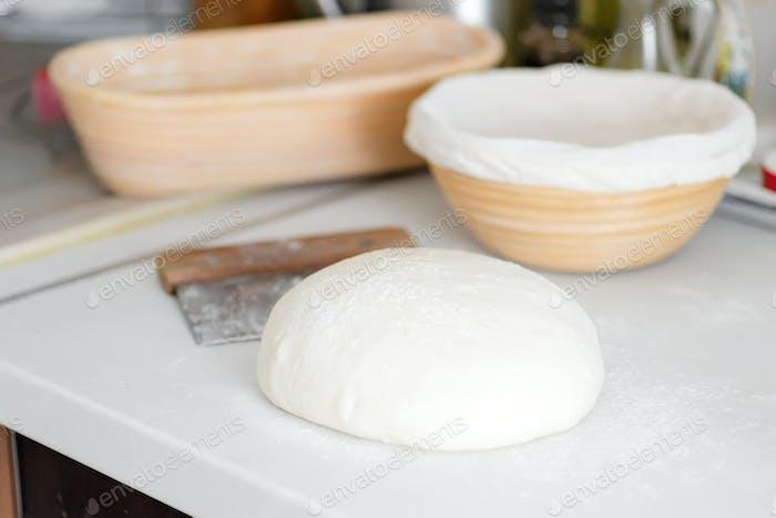 Hausgemachter frisch zubereiteter Teig für frische gesunde Backwaren und Gebäck auf einem weißen Küchentisch