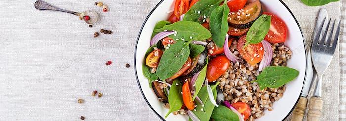 Buchweizensalat mit Kirschtomaten, roten Zwiebeln und frischem Spinat. Vegane Lebensmittel. Diät-Menü.