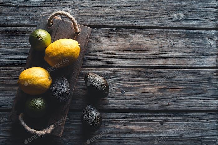 Avocado und Zitrone mit Messer auf altem Holzbrett, gesunde Ernährung, Vegetarismus, Wellness