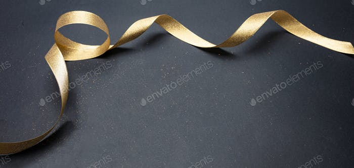 Golden satin ribbon on black background, copy space
