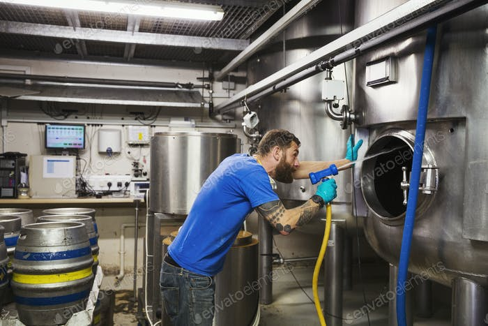 Man working in a brewery, cleaning inside of a large stainless steel kettle with a high pressure