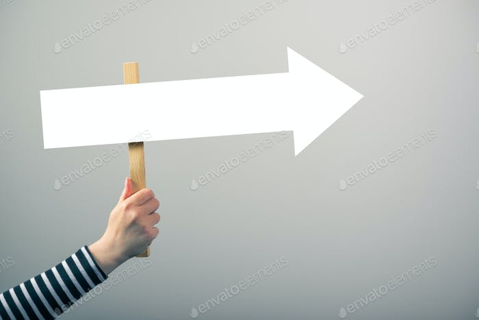 Woman holding guiding direction arrow sign