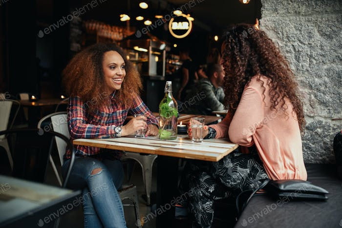 Two women sitting in a cafe talking