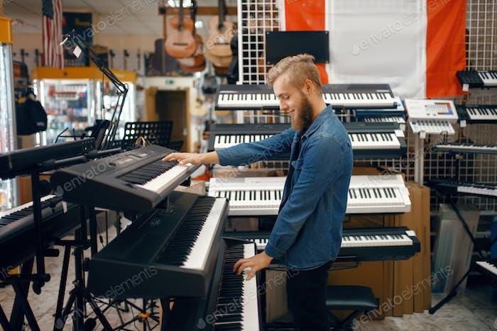 Junger Mann Wahl Synthesizer im Musikgeschäft