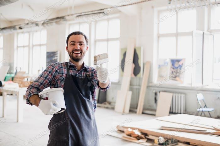 Счастливый молодой художник держит кисть и показывая его на камеру