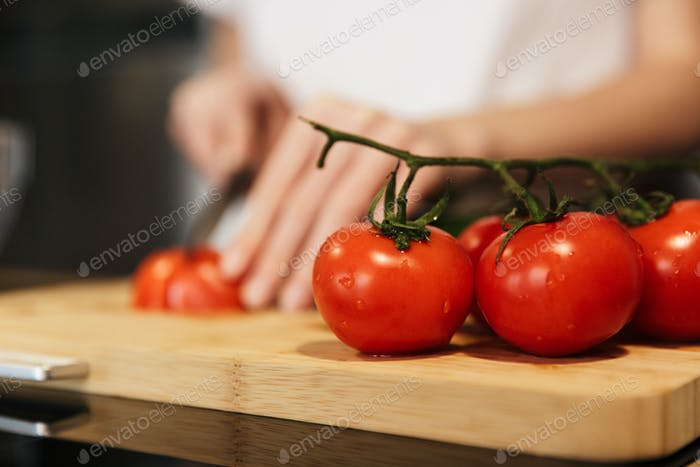 Close up of a woman slicing tomatoes for the salad