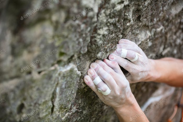 Rock climber's hands gripping hold on cliff