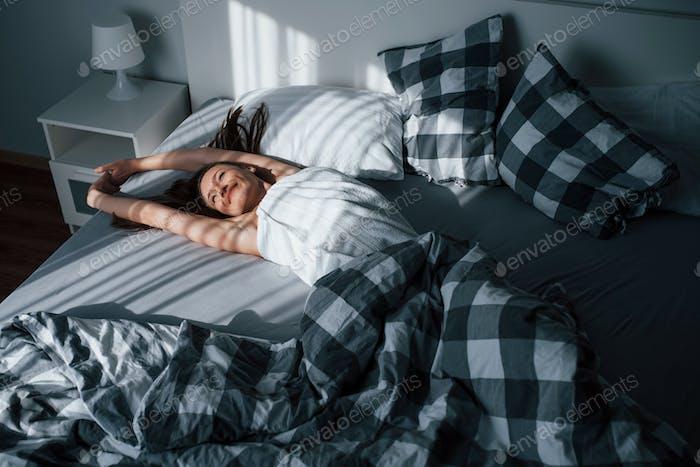 Hübsche junge Frau liegt morgens auf dem Bett in ihrem Zimmer