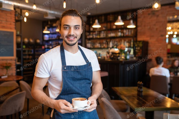 Young cheerful waiter in white t-shirt and blue apron holding cup of coffee