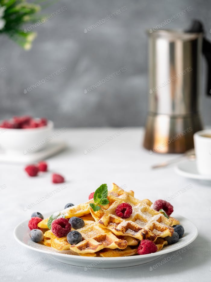 Belgian waffles with raspberries, blueberries, curd and coffee