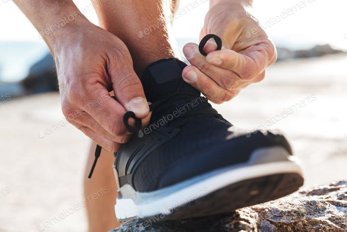 Close up of a man tying tying shoelace