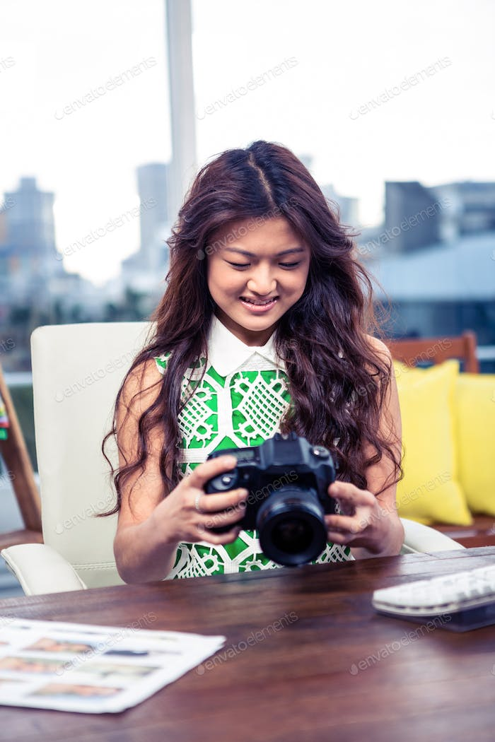 Smiling creative businesswoman holding camera in office