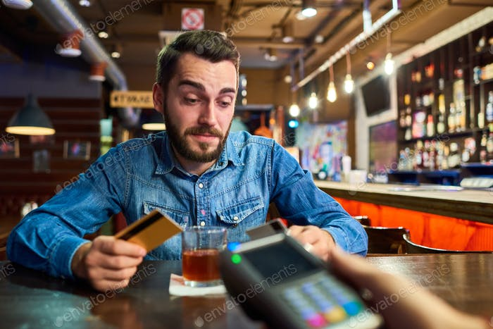 Drunk Man Paying via Credit Card in Pub