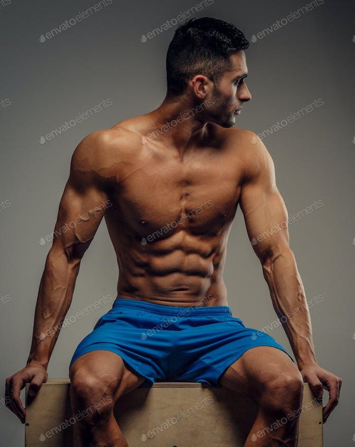 Muscular guy in blue shorts posing in studio.