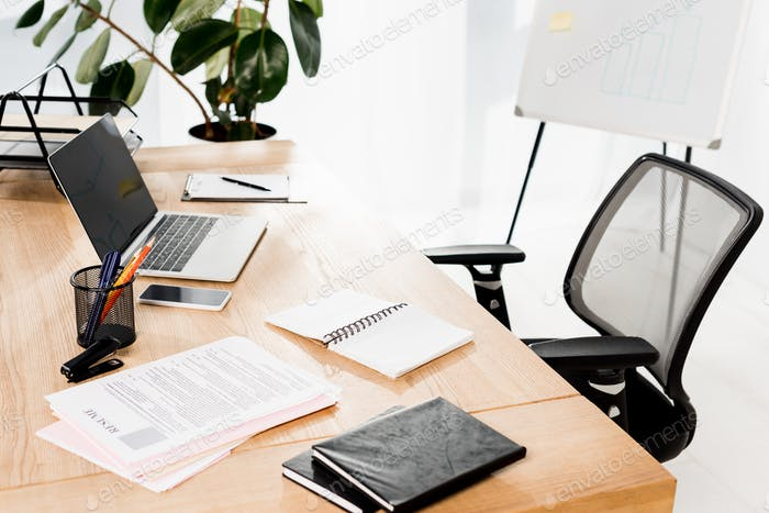 modern office with laptop, smartphone, resume and blank notebook on desk