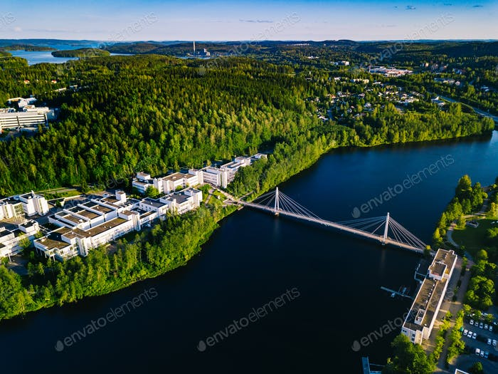 Aerial view of blue lake with cable-stayed bridge and green summer town in Finland.