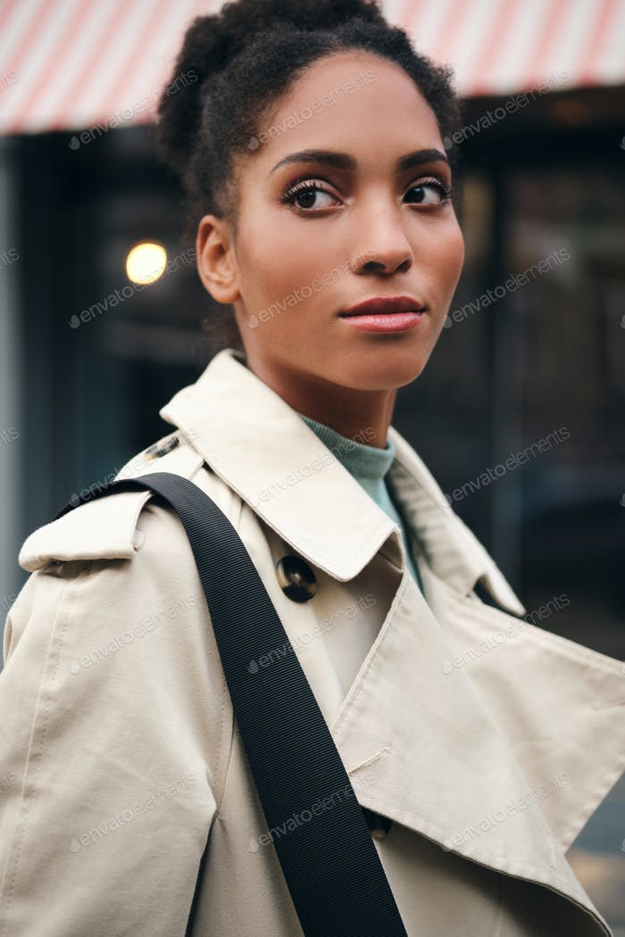 Portrait of beautiful African American casual girl in trench coat thoughtfully looking away outdoor