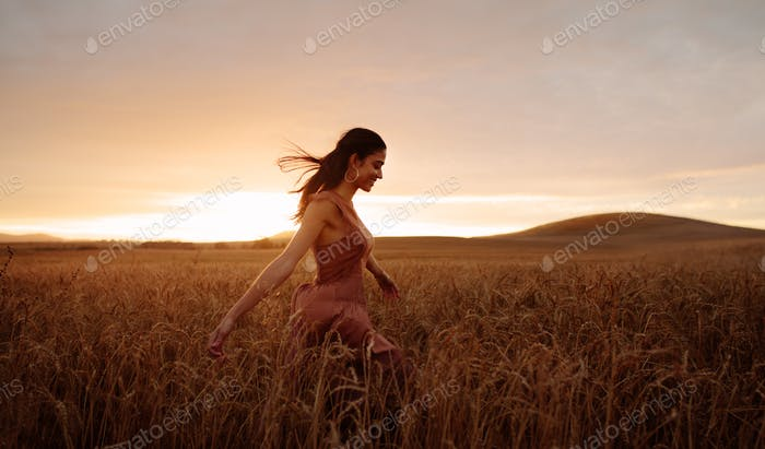 Carefree female strolling in the wheat field