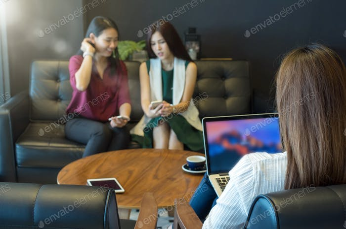 Reaw view of businesswomen using the computer over the couple of Asian Business women