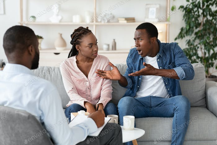 Anxious black man complaining about relationship problems with wife at counsellor's office