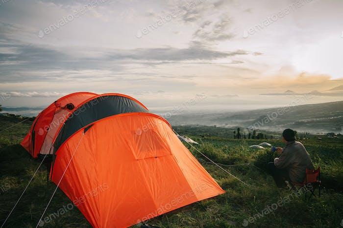 Asian man camping with sunrise view in mountain, Posong Temanggung, Indonesia