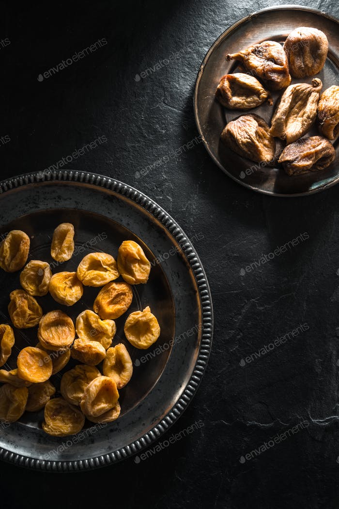 Dried figs and dried apricots on tin plates on a stone table