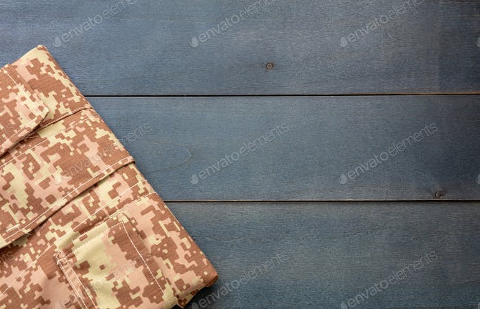 US army camouflage uniform on blue background, top view