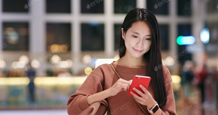 Woman check on the discount in mobile phone inside shopping mall