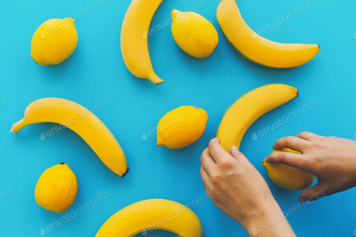 Yellow bananas and lemons on blue trendy paper background