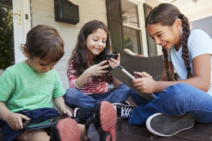 Gruppe von Kindern sitzen auf Veranda spielen mit digitalen Geräten