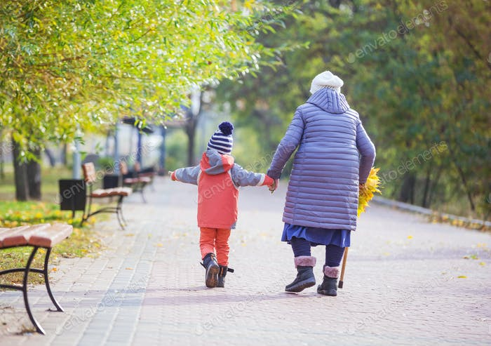 Little boy and great grandmother walking in autumn park