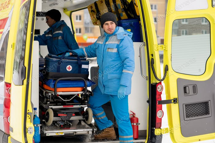 Male paramedic with first aid kit standing by stretcher in ambulance car